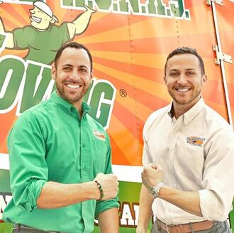 Omar Soliman and Nick Friedman stand in front of a College HUNKS Hauling Junk & Moving moving truck
