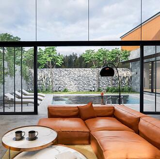Orange couch in living room. Doors opening to outdoor living space. An indoor outdoor living space is shown.