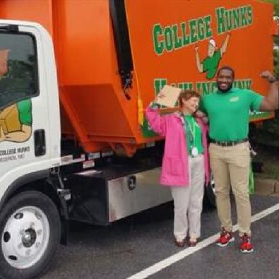 Dana Burton, College Hunks franchise owner, standing with a Hunk