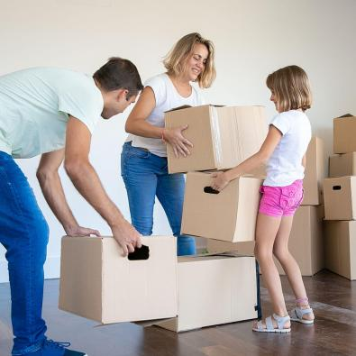 young family packing boxes to move to new home