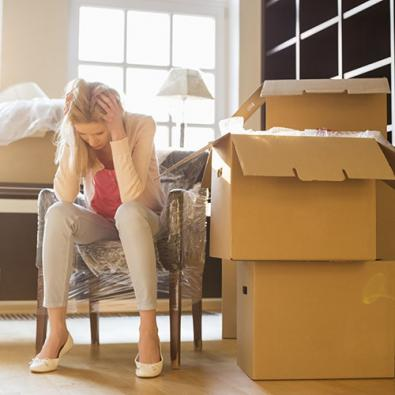 anxious woman sitting next to moving boxes