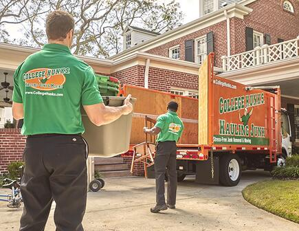 two college hunks moving items to a junk truck
