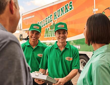 Two College HUNKS movers talking to a family