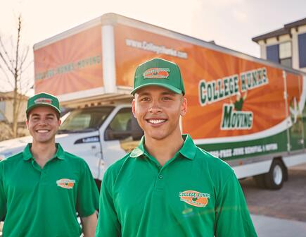 Two men wearing green College Hunks shirts, standing in front of a moving truck.