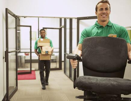 Two hunks moving things out of an office