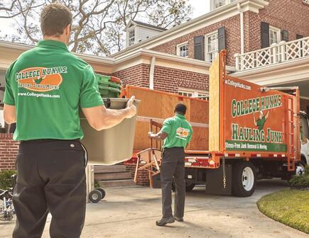 Two hunks hauling junk to orange truck