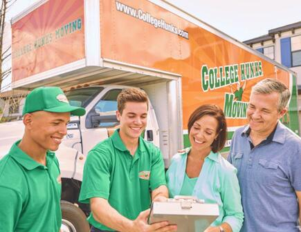 Two customers and two hunks in front of a moving truck reviewing documentation