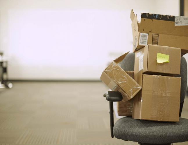 Stack of brown boxes on gray office chair