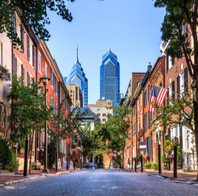 Philadelphia skyline view from a street full of traditional rowhouses.