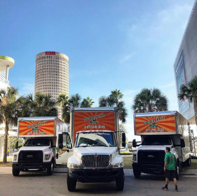 College HUNKS moving trucks with Downtown Tampa in the background.