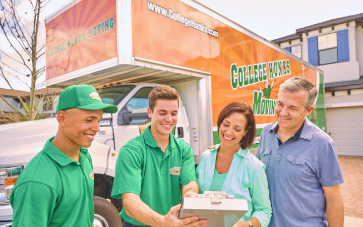 Two HUNKS and two customers reviewing documents in front of a College Hunks Hauling Junk moving truck