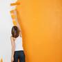Woman painting a wall orange