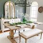 rustic dining room decorated in a farmhouse home decor style. Wooden table, mixed metal light fixture, greenery on the table